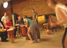 Left to right: Steve Kellar (hands), Toni Kellar and Andy Hall (sitting), and Matt Smith and Andy McVey (standing) drum for Molly Watson and dancers